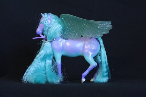 Cirra; Body Color: Purple and Teal <br/>Hair Color: Teal <br/>Wing Color: Teal <br/>Symbol: Cascading silver 4-point stars, dots, and moon <br/>Brush: Teal <br/> Accessories: 2 dark purple ribbons 1 silver ribbon, 2 long silver elastics <br/>Notes: Hinged wings flap manually