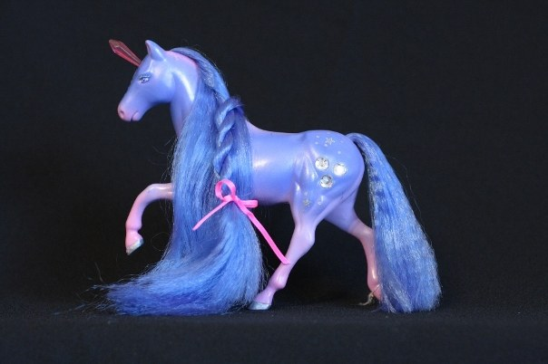 Prisma; Body Color: Blue, Purple, and Pink<br/>Hair Color: Dark Blue<br/>Horn Color: Pink <br/>Jewel Color: Silver<br/>Brush: Dark Blue <br/> Accessories: 2 Hot Pink Ribbons<br/>Notes: Front and back of mane is in a twisted braid, tail is also in a twisted braid secured with silver elastic. Body accented with silver stars and dots. Prisma's pose is only used by her.